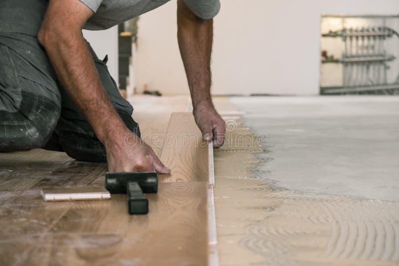Trabalhador que instala placas de revestimento de madeira fotografia de stock