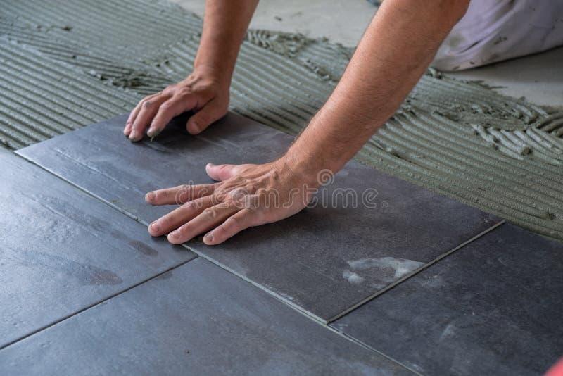 Trabalhador que instala telhas de assoalho cerâmicas foto de stock royalty free