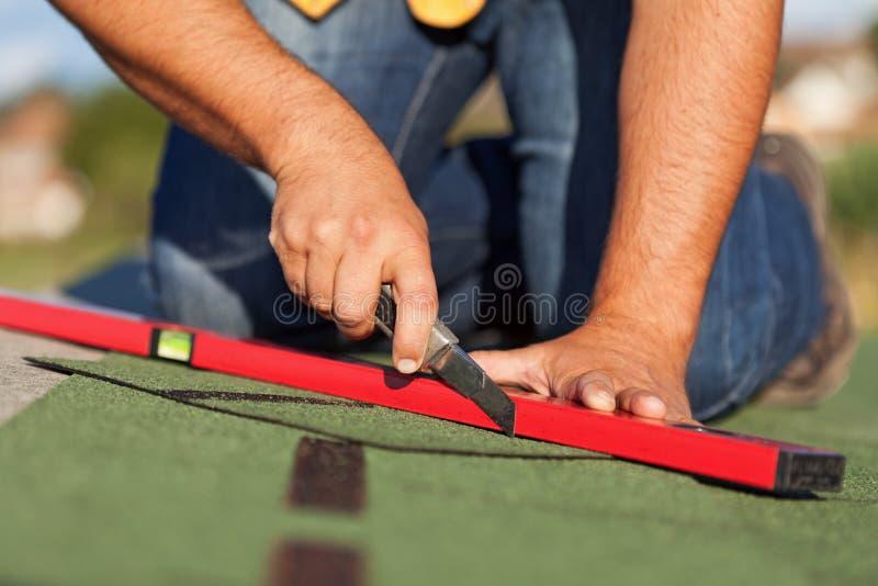 Trabalhador que instala telhas do telhado do betume foto de stock
