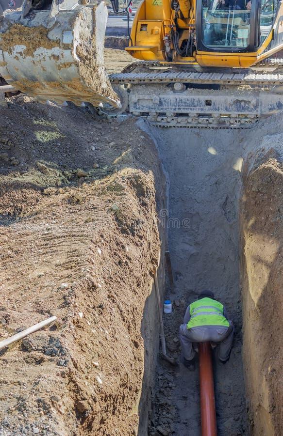 Trabalhador que instala a tubulação de esgoto na trincheira 2 foto de stock royalty free