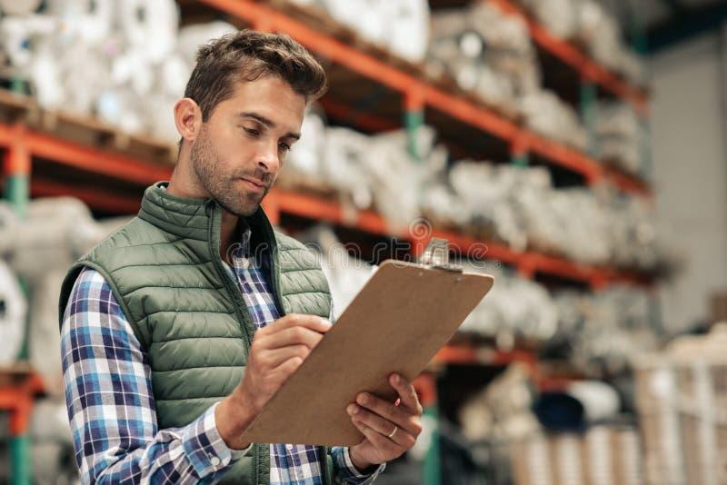 Trabalhador que lê um inventário ao estar em um assoalho do armazém fotos de stock