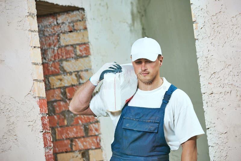 Trabalhador que leva o saco do cimento imagens de stock