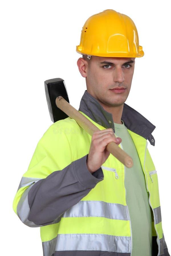 Trabalhador que leva um malho foto de stock