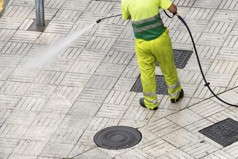 Trabalhador que limpa o passeio da rua com o jato de ?gua de alta press?o fotografia de stock