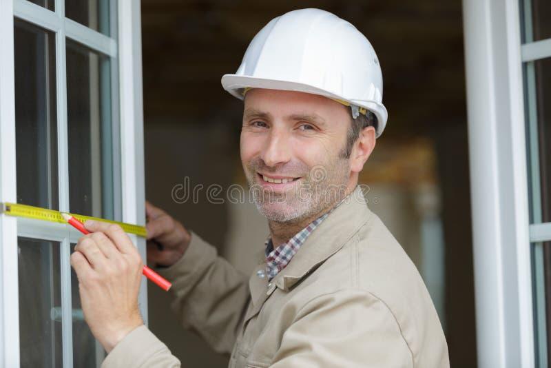 Trabalhador que mede a janela vitrificada dobro fotografia de stock royalty free