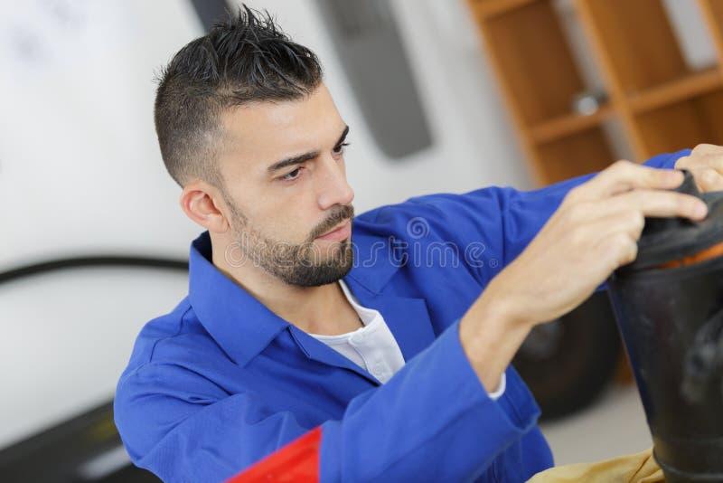 Trabalhador que monta algo na oficina fotografia de stock royalty free
