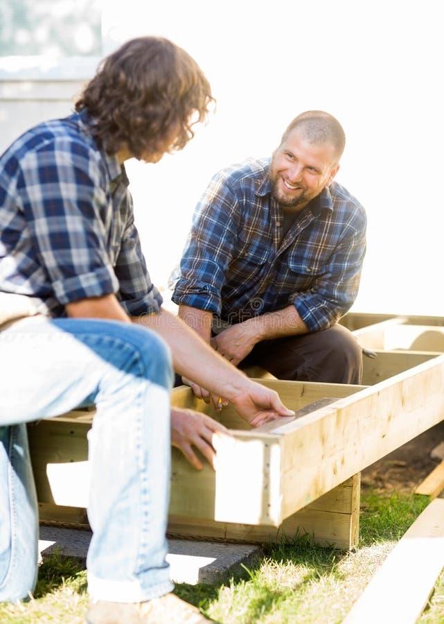 Trabalhador que olha a madeira de medição do colega de trabalho no local imagem de stock royalty free