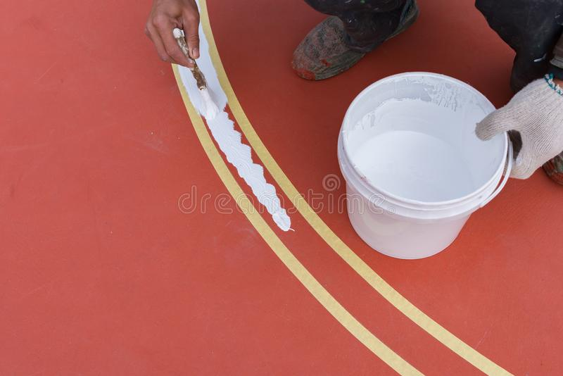 Trabalhador que pinta a atividade secundárioa no assoalho para o estádio exterior imagem de stock