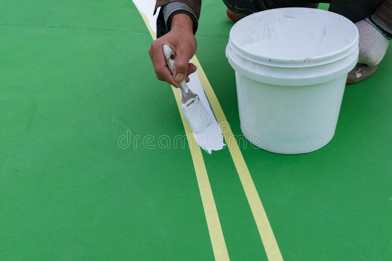 Trabalhador que pinta a atividade secundárioa no assoalho para o estádio exterior imagens de stock