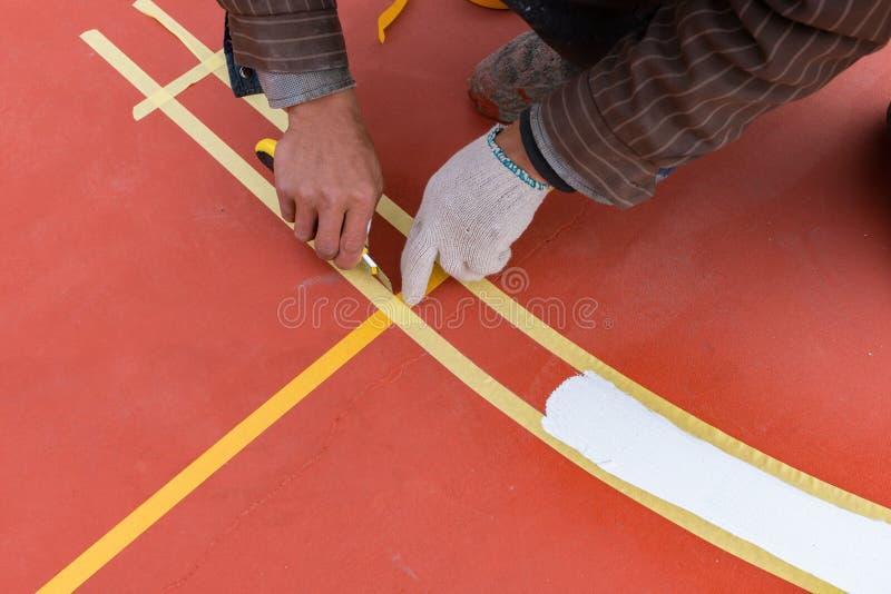 Trabalhador que pinta a atividade secundárioa no assoalho para um estádio exterior imagem de stock