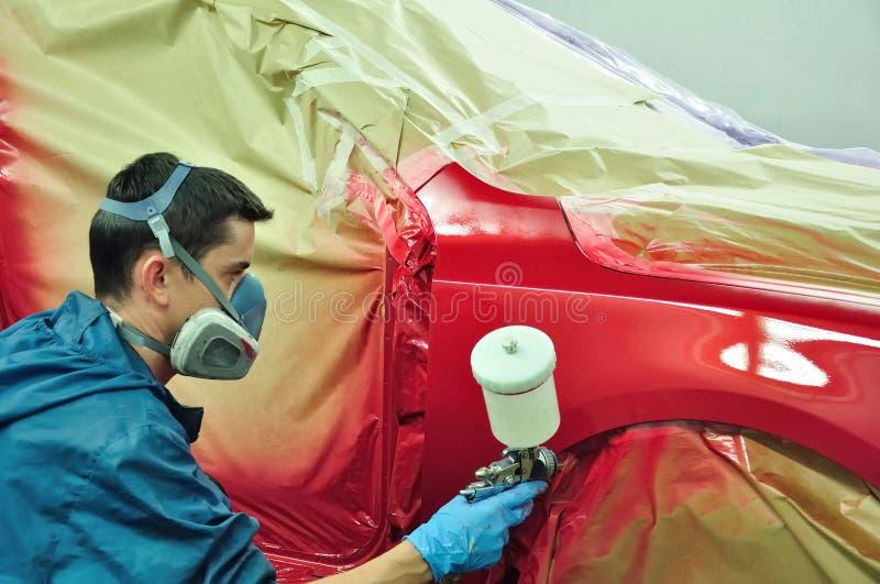 Trabalhador que pinta um carro. imagem de stock royalty free
