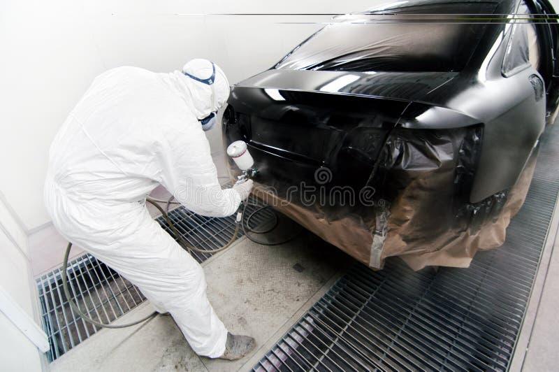 Trabalhador que pinta um carro na garagem usando uma arma do aerógrafo fotografia de stock royalty free