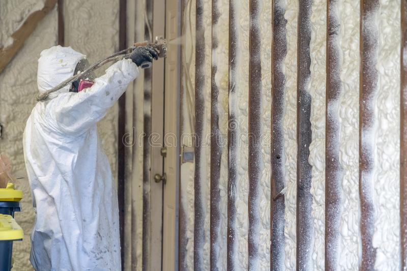 Trabalhador que pulveriza a isolação fechado da espuma do pulverizador da pilha em uma casa imagens de stock