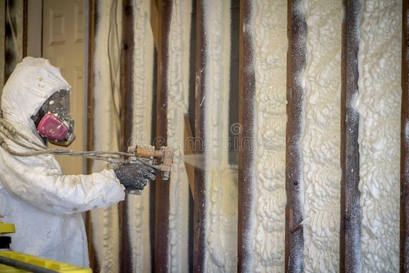 Trabalhador que pulveriza a isolação fechado da espuma do pulverizador da pilha em uma parede home imagem de stock