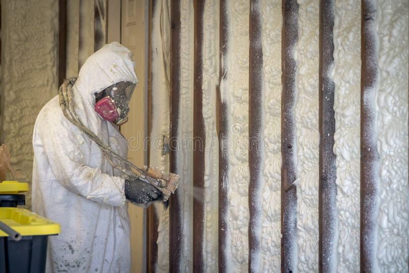 Trabalhador que pulveriza a isolação fechado da espuma do pulverizador da pilha em uma parede home imagens de stock