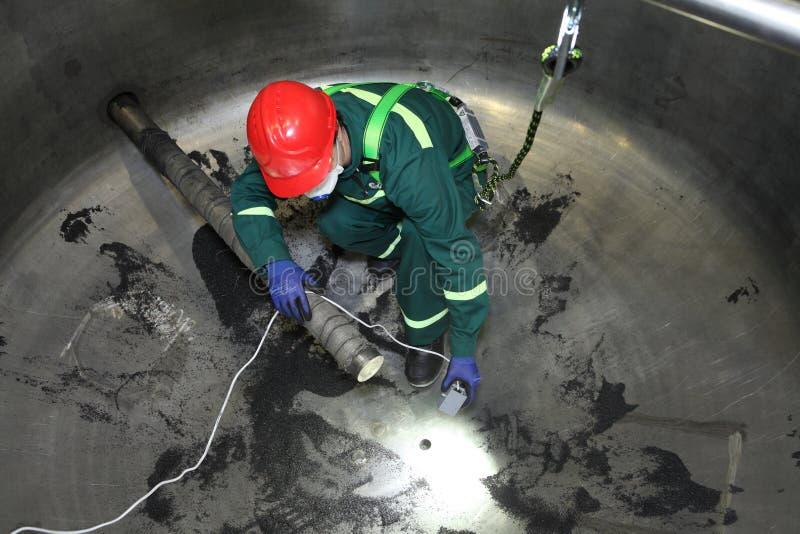 Trabalhador que senta-se dentro de uma caldeira industrial de aço durante o PR do reparo fotos de stock