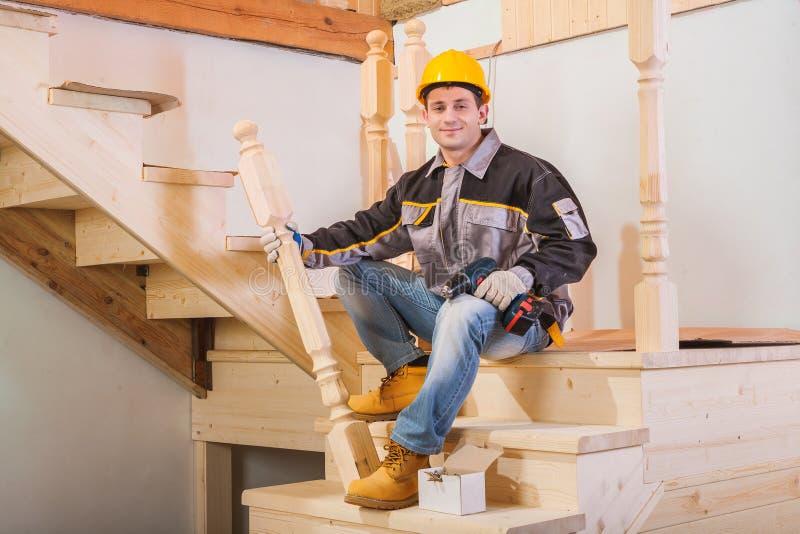 Trabalhador que senta-se na escada que guarda o cargo de madeira e a broca sem corda imagens de stock