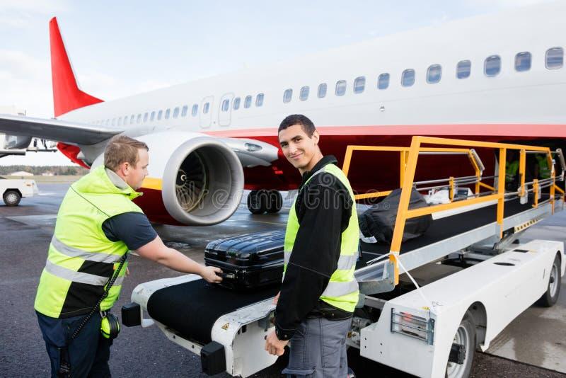 Trabalhador que sorri quando colega que descarrega a bagagem na pista de decolagem fotos de stock royalty free