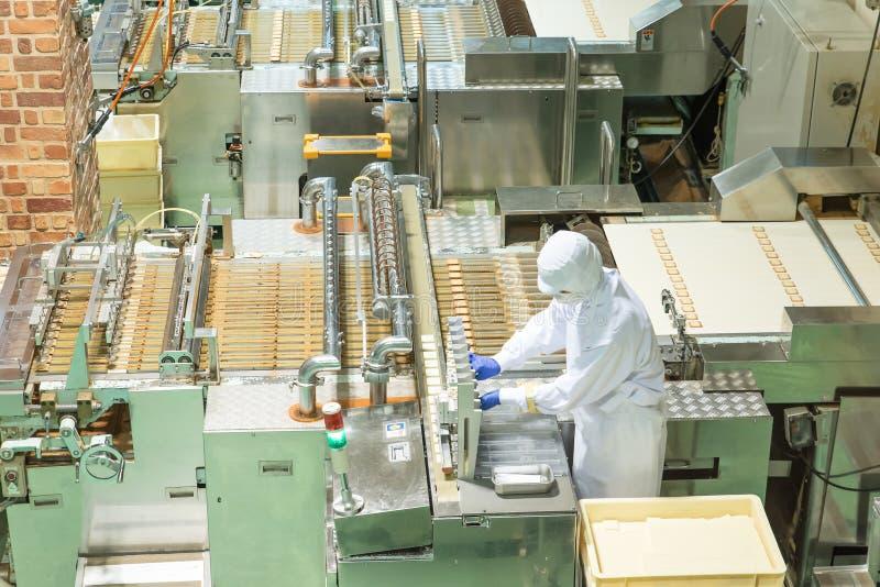 Trabalhador que trabalha com a máquina na fábrica da padaria imagens de stock royalty free