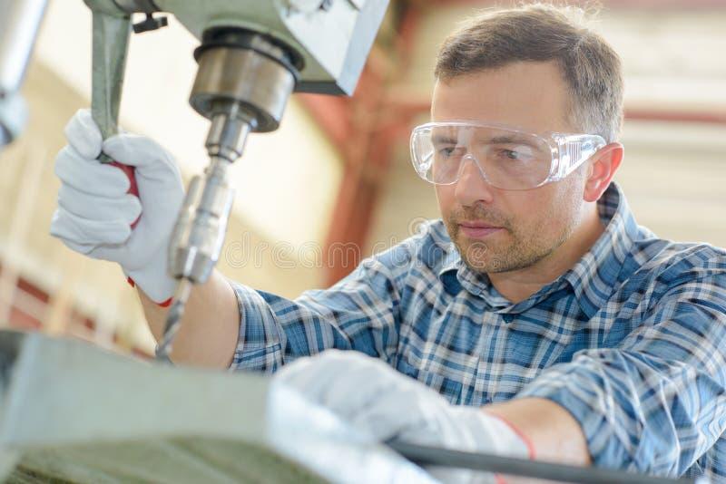 Trabalhador que usa a broca do banco fotografia de stock