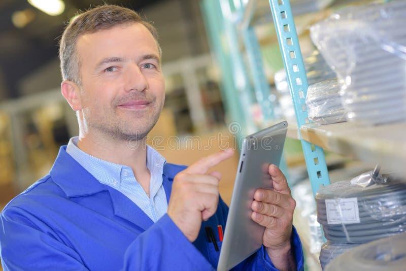 Trabalhador que usa a tabuleta para armazenar a informação imagens de stock royalty free