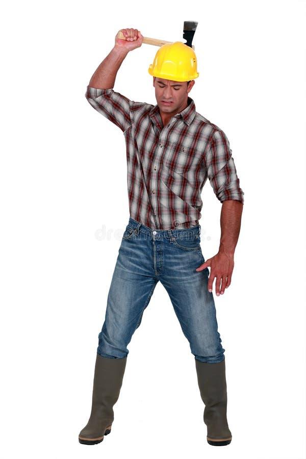 Trabalhador que usa um machado fotos de stock