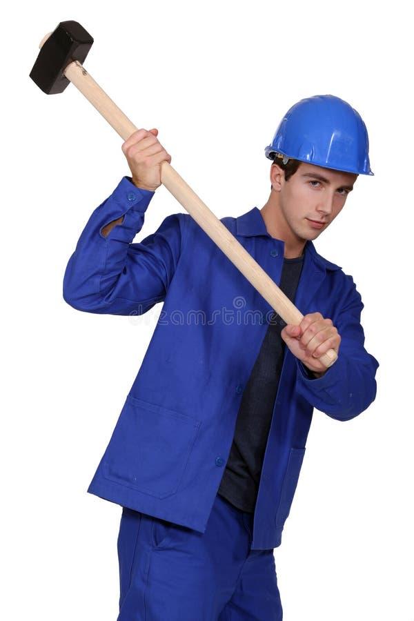 Trabalhador que usa um martelo de pequeno trenó imagens de stock royalty free