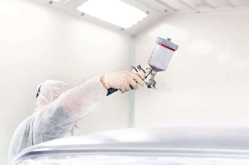 Trabalhador que usa uma arma de pulverizador da pintura imagem de stock royalty free