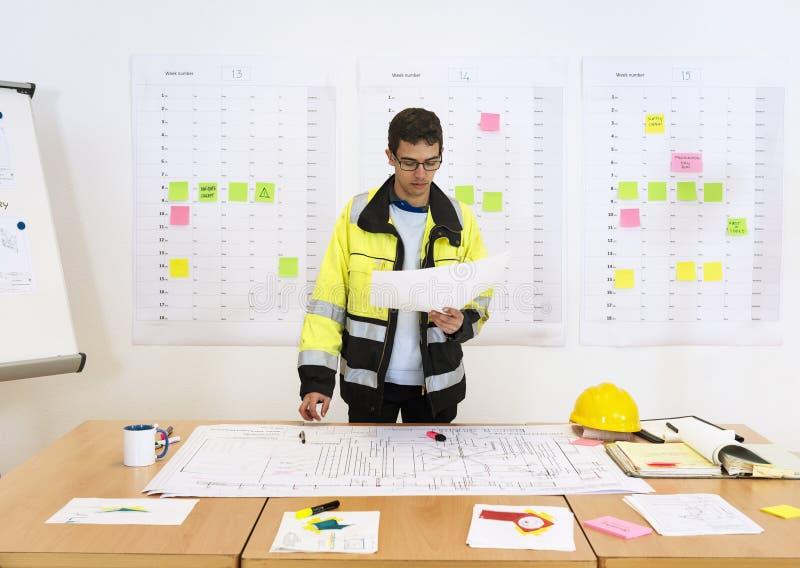 Trabalhador que verifica desenhos técnicos foto de stock