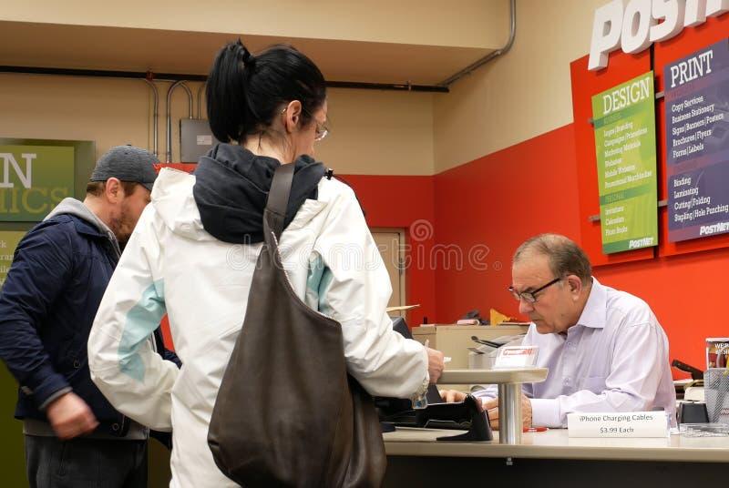 Trabalhador que verifica o pacote para ver se há o cliente na estação de correios imagens de stock