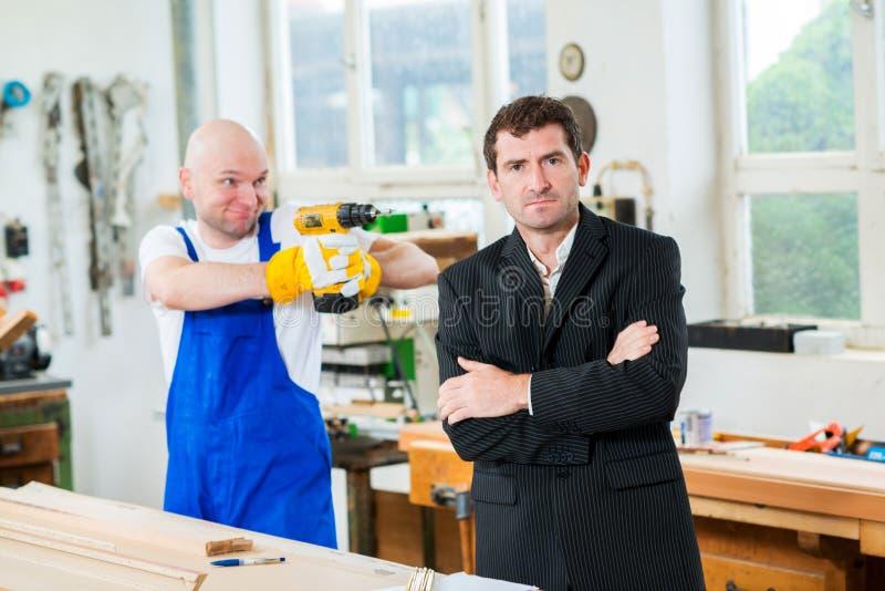 Trabalhador que visa seu chefe com máquina de perfuração foto de stock
