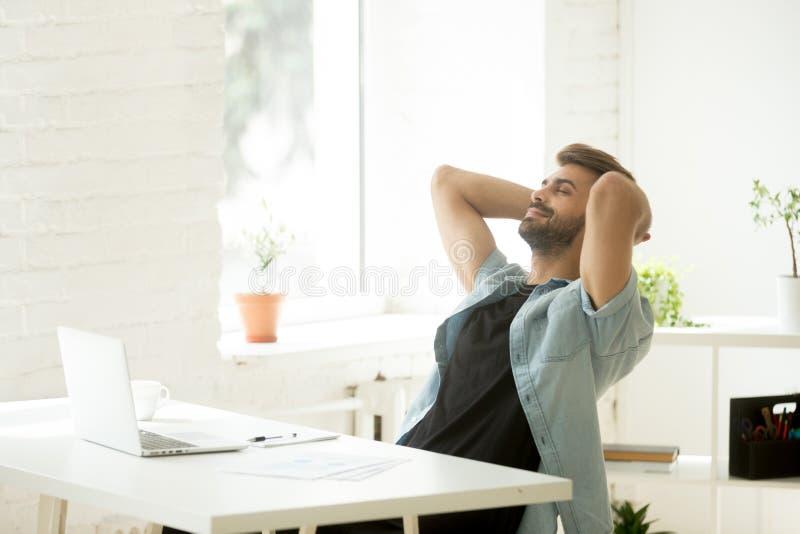 Trabalhador relaxado de sorriso que inclina-se para trás na cadeira durante a ruptura de trabalho fotografia de stock royalty free