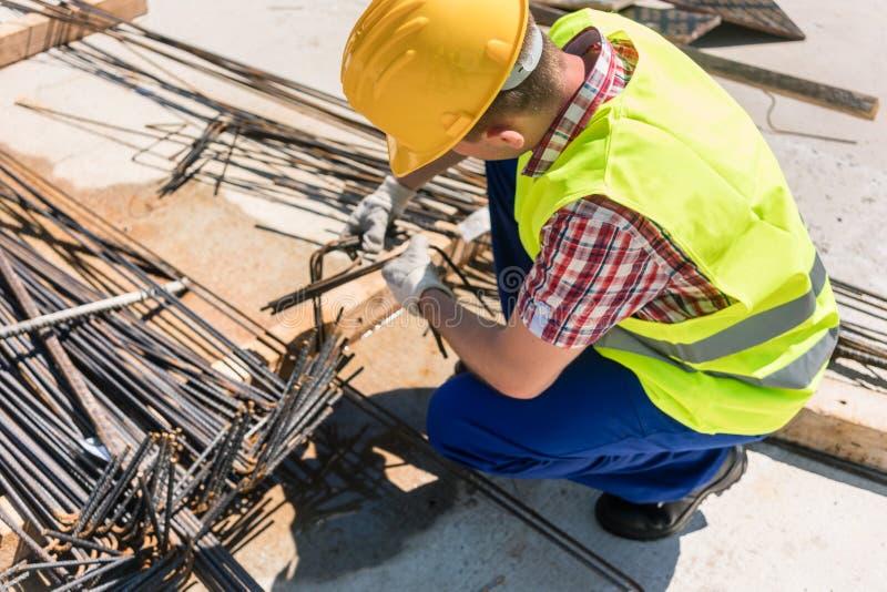 Trabalhador seguro que verifica a qualidade das barras de aço fotografia de stock