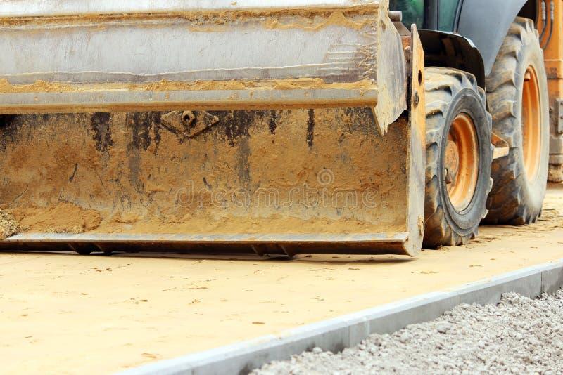 trabalhador sujo do carregador de cubeta que trabalha na praça da cidade movendo páletes de pavimentos foto de stock