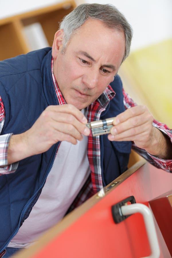 Trabalhador superior que guarda o tambor da fechadura da porta imagem de stock