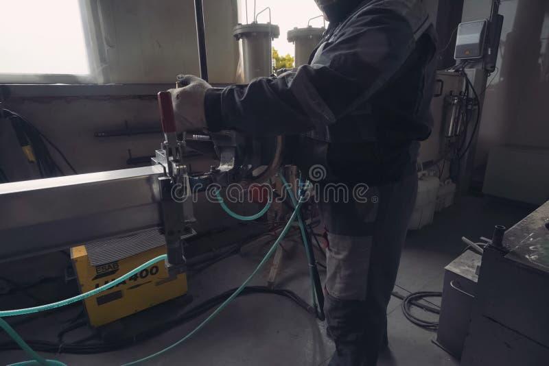 Trabalhador trabalha em uma fábrica de equipamentos climáticos imagem de stock