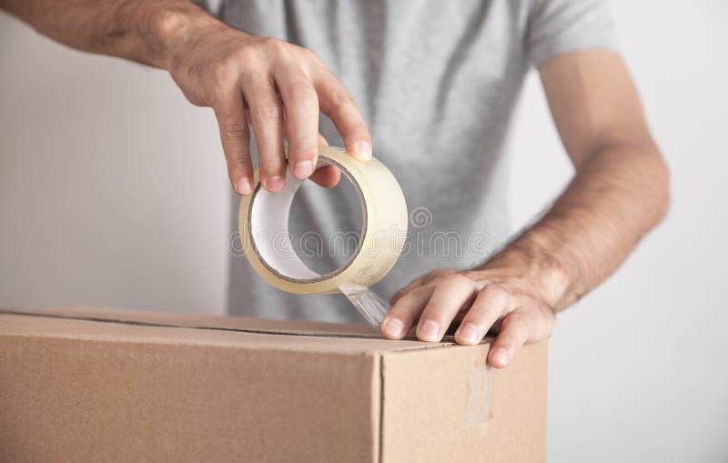 Trabalhador usando caixa de papelão de selagem de fita Produtos, Comércio, Varejo, Entrega foto de stock royalty free