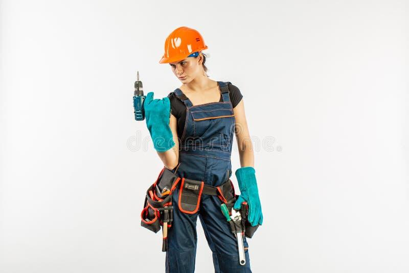 A trabalhadora braçal 'sexy' nos macacões e o capacete de segurança com ferramenta cercam guardar a broca elétrica, no fundo bran foto de stock