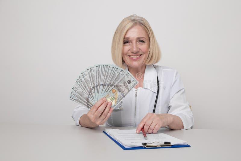 Trabalhadora de medicina feminina em gabinete sorrindo e segurando dinheiro isolado imagem de stock