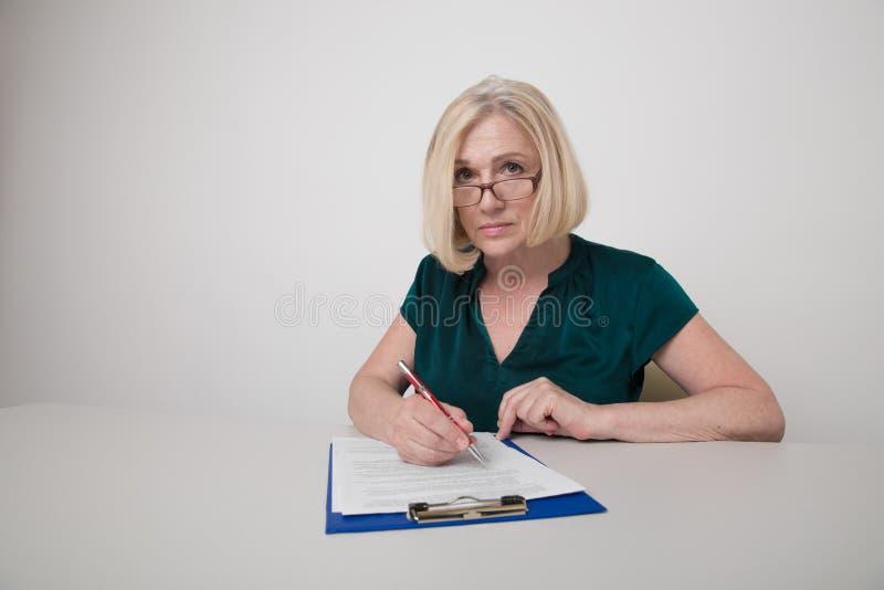 Trabalhadora profissional de escritório escrevendo em papel isolado imagens de stock