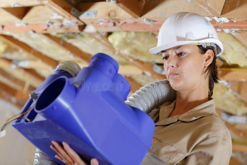 Trabalhadoras do sexo feminino que instalam o sistema de ventilação no teto dos edifícios imagem de stock royalty free