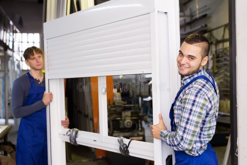 Trabalhadores com a janela diferente do PVC com obturador foto de stock royalty free