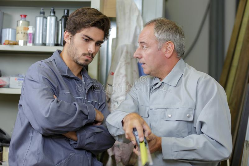 Trabalhadores com marcação de medição da fita foto de stock