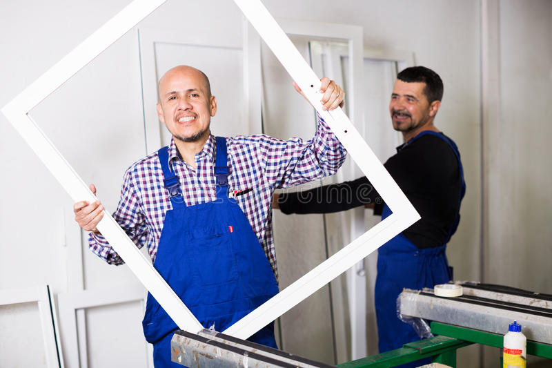 Trabalhadores com perfis terminados do PVC imagem de stock