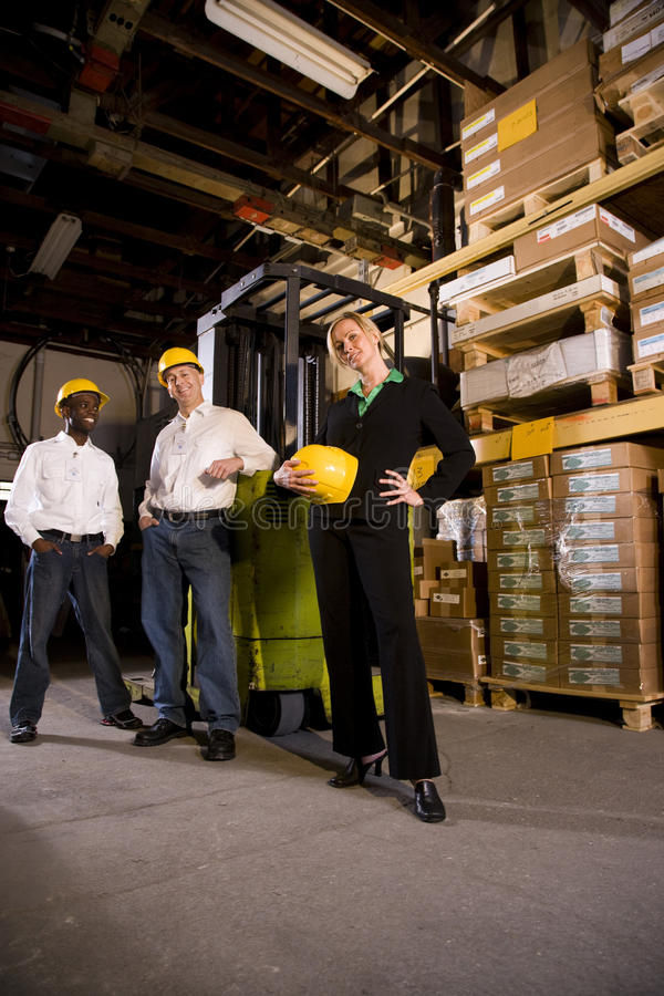 Trabalhadores com a saliência fêmea no armazém de armazenamento fotografia de stock royalty free
