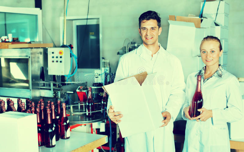 Trabalhadores da adega que guardam o pacote da caixa com garrafas de vinho imagem de stock