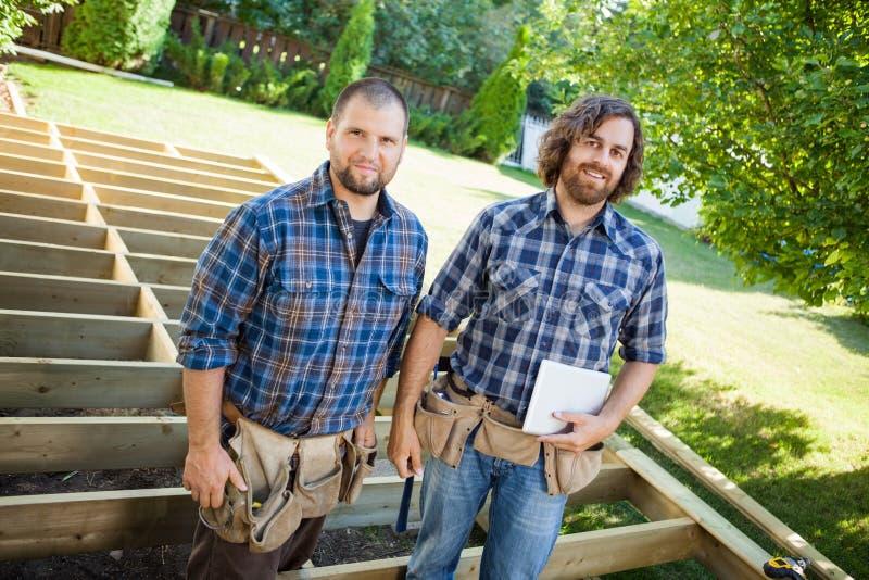 Trabalhadores da construção com a tabuleta de Digitas em fotografia de stock
