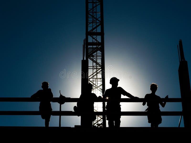 Trabalhadores da construção do telhado em uma ruptura, retroiluminada fazendo lhes shilouettes fotos de stock