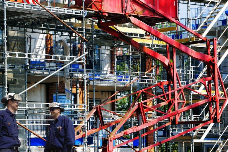 Trabalhadores da construção e terreno de construção gigante fotografia de stock