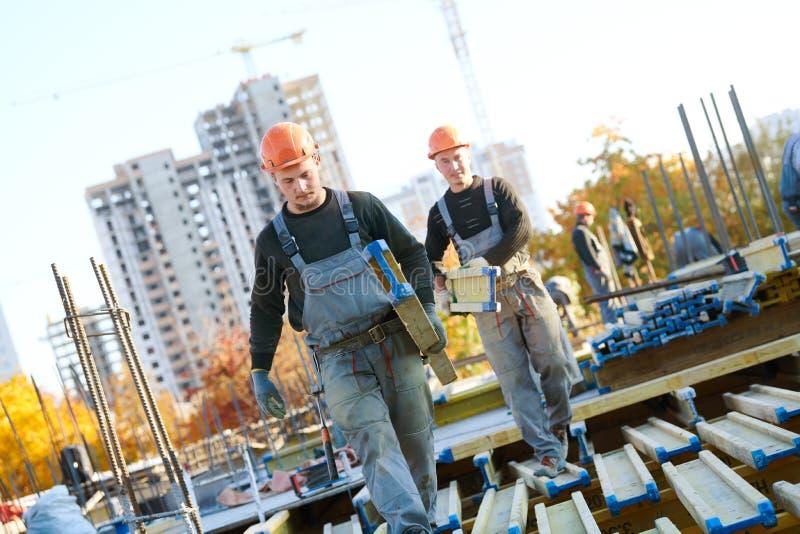 Trabalhadores da construção na área da construção que instala o wormwork imagem de stock